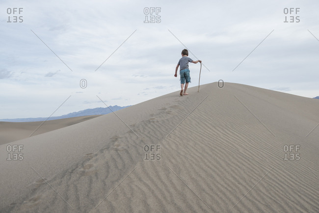 Boy walking with stick on Mesquite Flat Sand Dunes in Death Valley National Park, California, USA