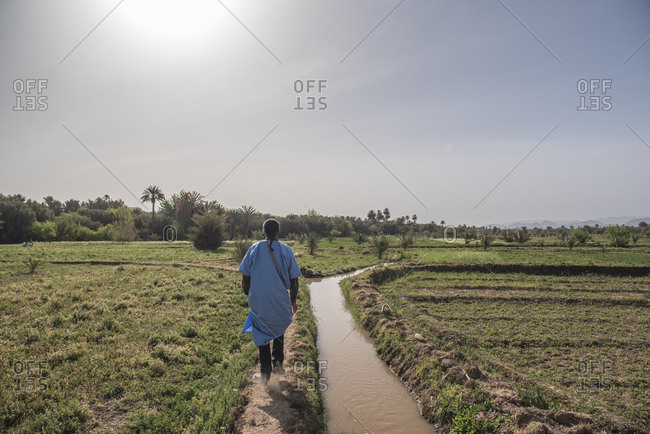 Berber tour guide walking through field near Ouarzazate, Morocco