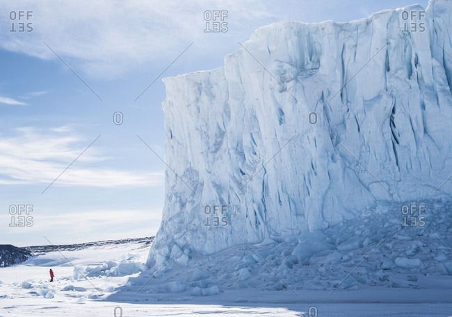 A woman stands next to the Barne Glacier in McMurdo Sound Antarctica.