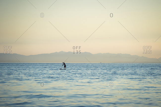 Standing up paddle boarder paddling on Vancouver's English Bay at dusk, British Columbia, Canada