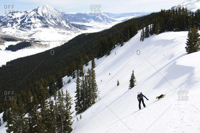 Snowboarder with his dog in tow.