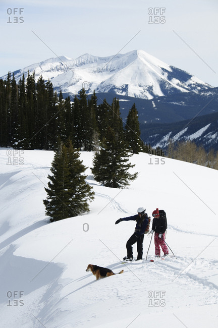 Two snow hikers with their dog.