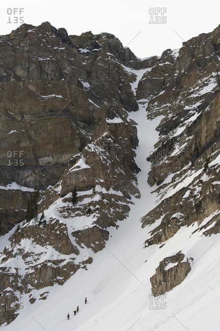 Backcountry snowboarders hiking up a chute