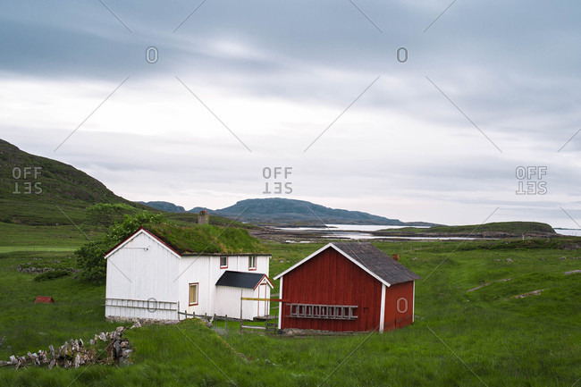 Old farm house and barn in a green field along the coast on the island of  in Norway