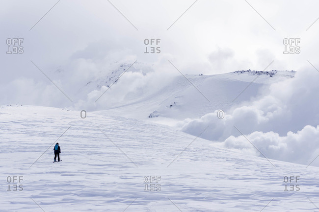 A snowboarder touring up Mt. Asahi towards the fume holes