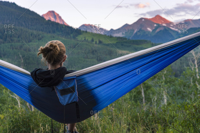 Young female in hammock looking at mountain peaks during sunset