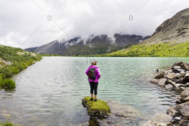 Young female stands on rock in a high alpine lake in Colorado