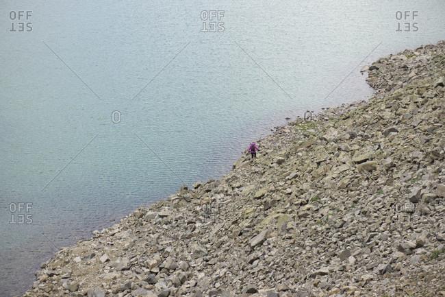 Young female hikes along a lake shore on rocks