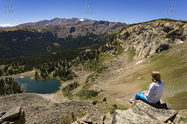 A young female sits on a rock edge in the mountains over looking a lake below