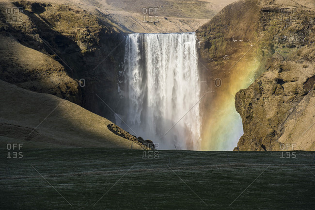 Rainbow in front of splashing waterfall, Iceland