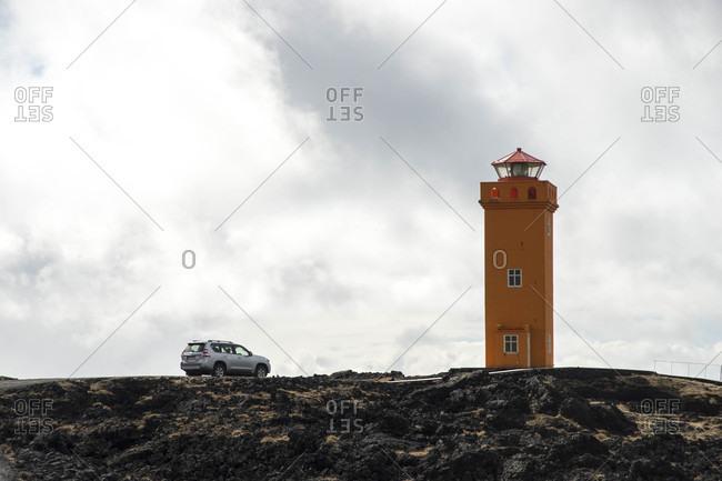 SUV parking next to orange lighthouse in Iceland