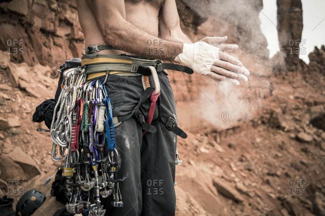 Rock climber applying chalk on hands, Moab, Utah, USA