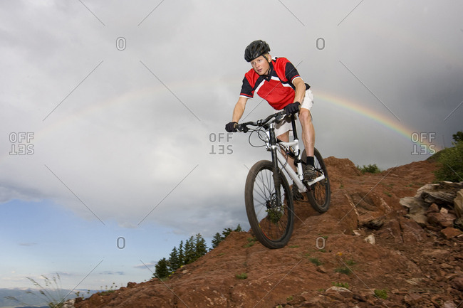 A man riding his bike under a rainbow on a rainy day in Utah.