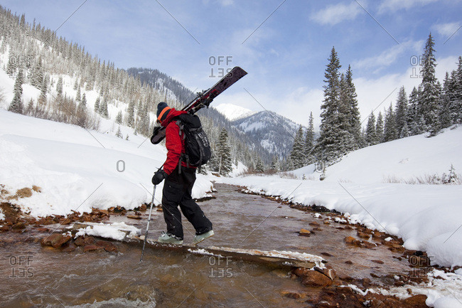 A  man carries his skis across a snowy, mountain stream.