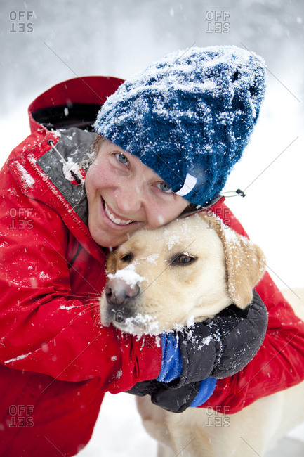 A woman gives her dog a loving hug on a snowy winter day.