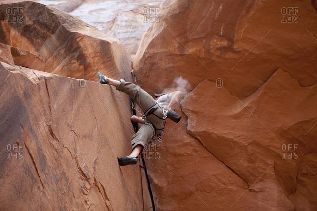 A man rock climbing outside of Moab, Utah.