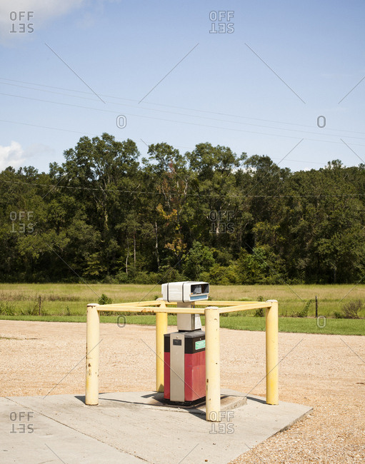 An old gas pump in an empty gas station parking lot