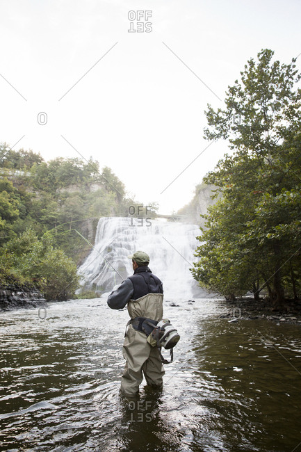 A fly fisherman casts his line in a river in front of a waterfall in upstate New York
