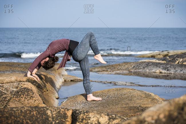 Woman doing yoga on rocky coastline