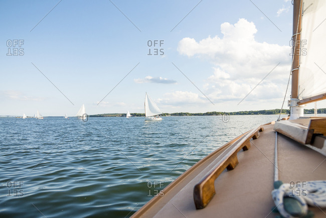 View from boat deck with sailboats in sea