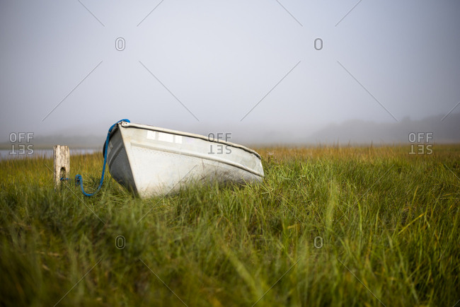 Rowboat sitting in grass in foggy Nantucket Marsh, Nantucket, Massachusetts, USA