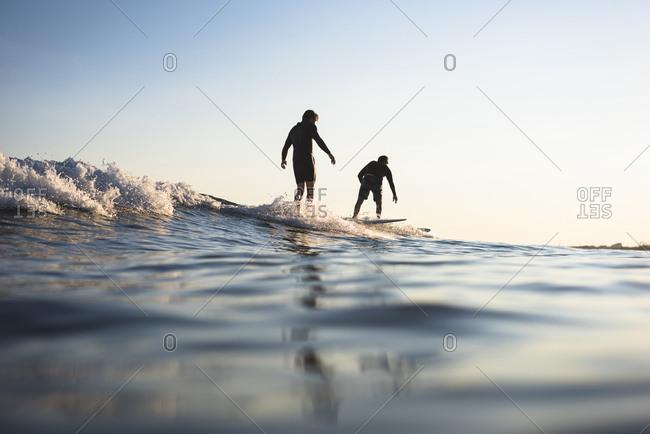 Surfers riding wave, Narragansett, Rhode Island, USA