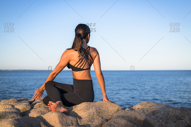 Woman doing yoga on seashore, Narragansett, Rhode Island, USA