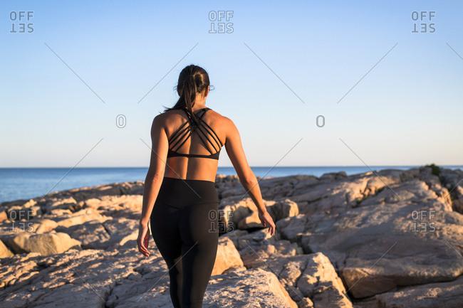 Woman in sportswear walking on seashore, Narragansett, Rhode Island, USA
