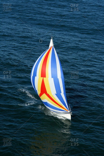 Aerial view of a sailing yacht with a colorful spinnaker cruising in Pittwater on the North Shore from Sydney, Australia.