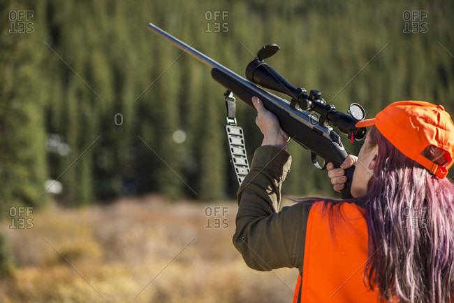 Female hunter aiming rifle, Colorado, USA