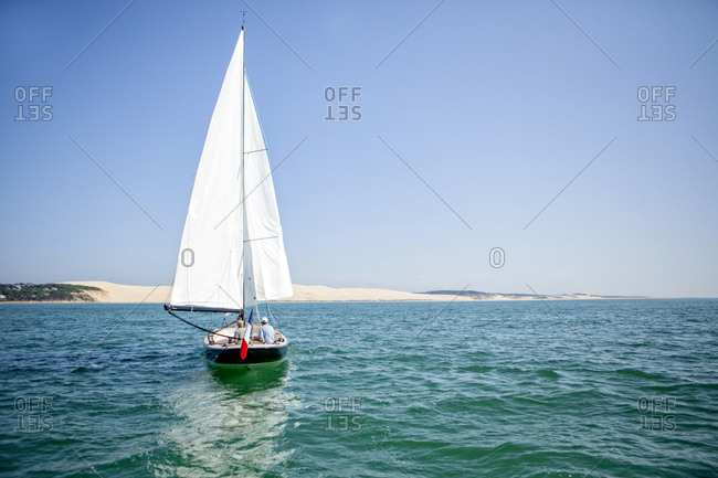 Sailboat sailing with Dune of Pilat in background, Banc d'Arguin, Arcachon Bay, France