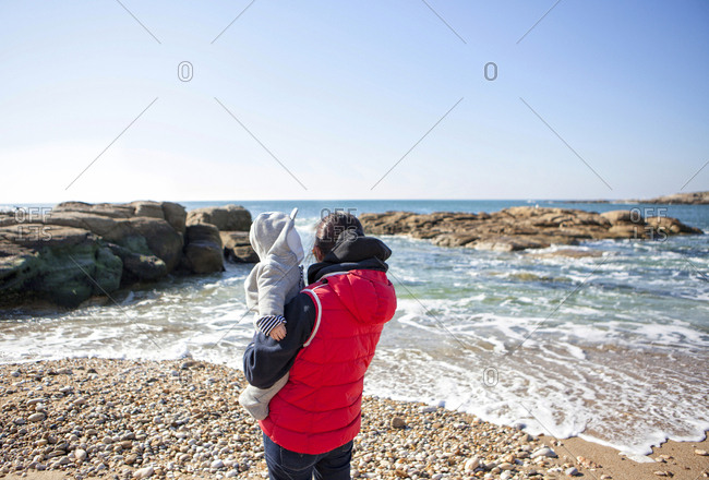 Mother and her baby boy watching ocean from shore, Kerroch, Brittany, France