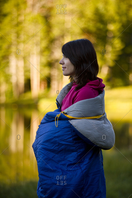 A woman wrapped in a sleeping bag enjoys the peace of Utah's Uinta Mountains.