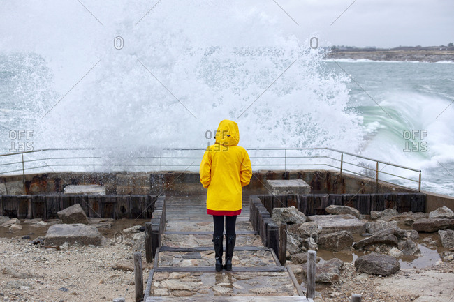 Woman looking at crashing waves on seashore, Kerroch, Brittany, France