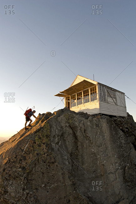 Mountaineer reaches the summit of Mt. Three Fingers in the Boulder River Wilderness,