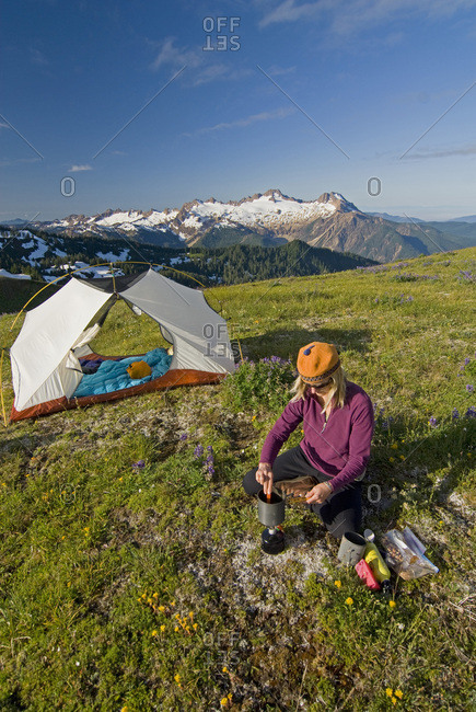 A female backpacker cooks breakfast on Grouse Ridge, Mt. Baker Wilderness, Washington State.