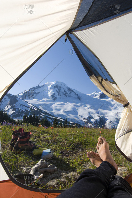 A camper relaxes at camp high on Skyline Divide, looking out at the majestic Mt. Baker, in the Mt. Baker Wilderness, Washington State.