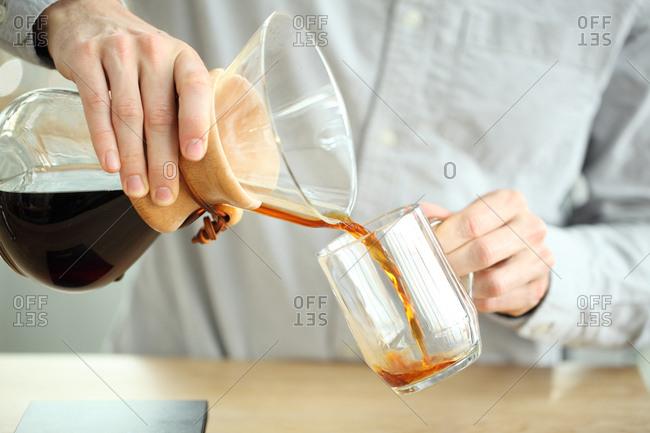 Barista pouring coffee into mug, Oakland, California, USA