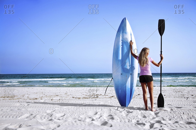 A girl holds up her sea kayak and paddle on Pensacola Beach, Florida.