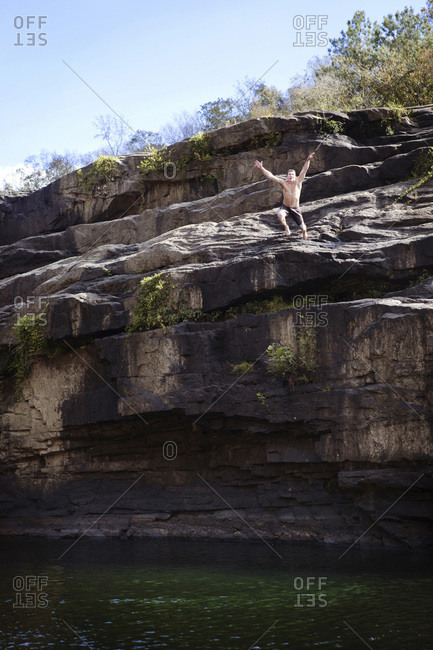 Young man jumps off rock cliffs into a lagoon at High Falls Park, Geraldine, Alabama.