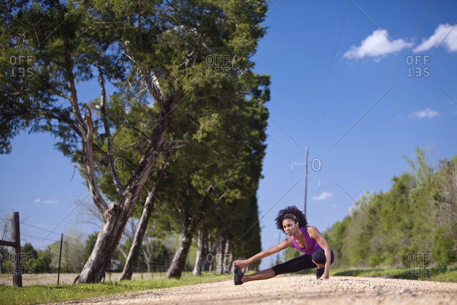 A woman stretches her legs looking off into the distance before going on a run.