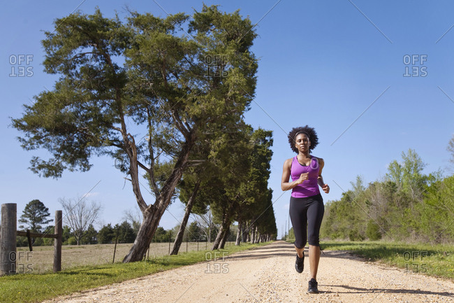 A woman runs down a dirt road lined with evergreen trees.