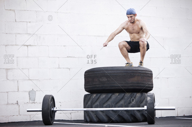 A young man jumps on tires while doing a fitness boot camp.