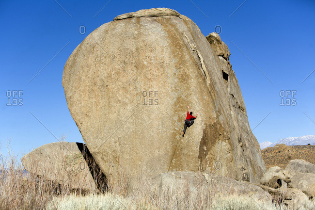 Male lead climbing on a boulder