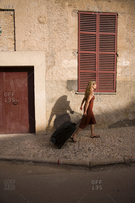 A woman pulls her luggage through a small town while on vacation.
