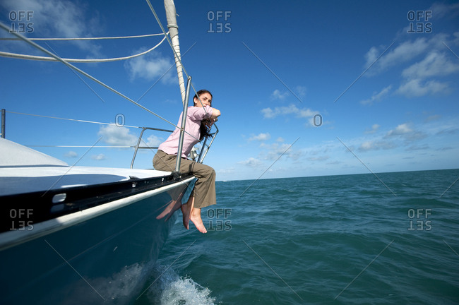 A woman sits on the bow of a boat off of Florida.