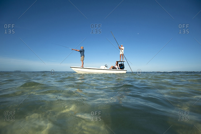 A couple fish as a man pilots a small boat in Florida.