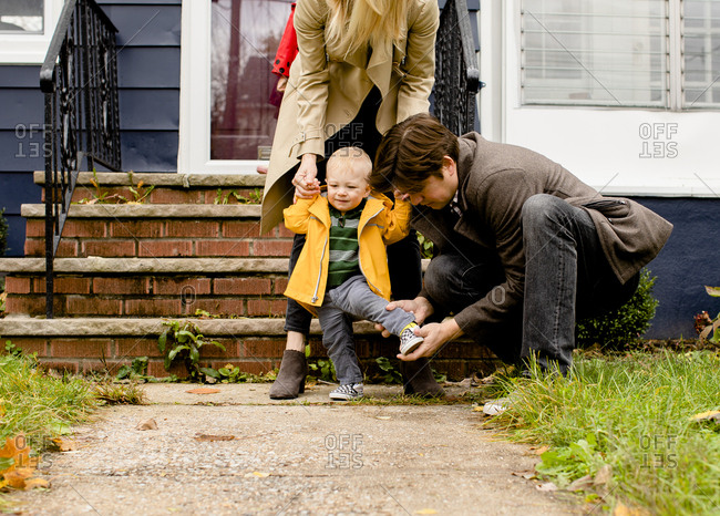 Parents getting baby dressed outside house