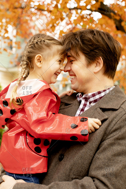Cheerful father and daughter rubbing noses during autumn