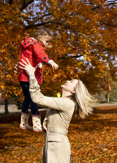 Cheerful mother playing with daughter at park during autumn